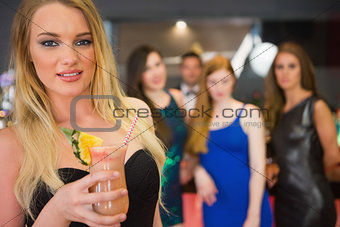 Blonde woman standing in front of her friends holding cocktail