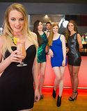 Beautiful blond woman holding cocktail standing in front of her friends