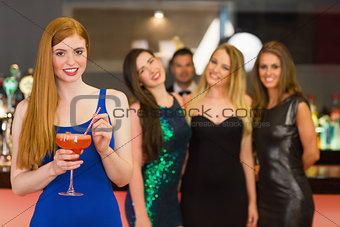 Attractive woman holding cocktail standing in front of her friends