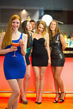 Smiling woman standing in front of her friends holding cocktail