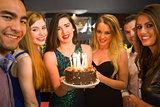 Happy friends celebrating brithday one holding birthday cake