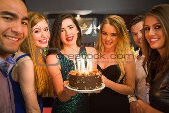 Happy friends celebrating brithday one holding birthday cake