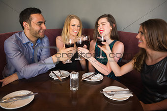 Laughing friends sitting together clinking glasses