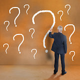 Mature businessman touching question mark