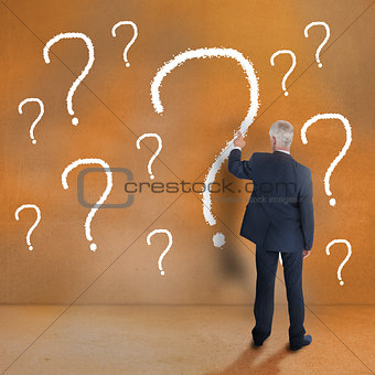 Mature businessman touching question mark