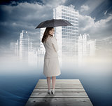 Smiling businesswoman standing on bridge in front of white city