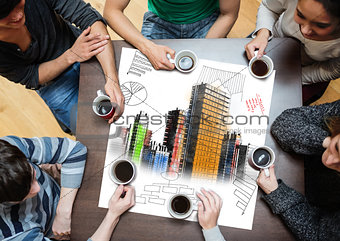 Overhead view of people sitting around table with painted city on sheet