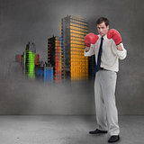 Businessman with boxing gloves standing in front of grey wall
