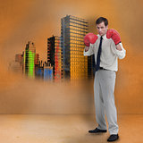 Businessman with boxing gloves standing in front of colored city