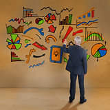 Rear view of mature businessman pointing at illustrations