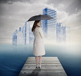 Rear view of businesswoman holding umbrella in front of holographic city
