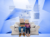 Couple with cartons on head sitting on couch under holographic finger print
