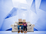 Couple with cartons on head sitting on couch under white holographic lock