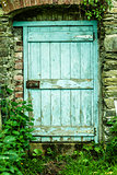 Blue wooden door in a stone wall