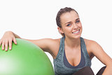 Smiling sporty woman sitting next to a fitness ball