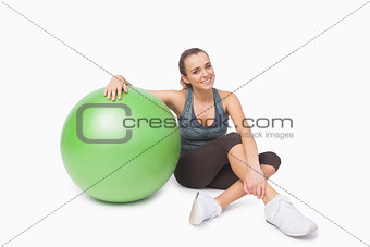 Cute woman sitting next to a fitness ball