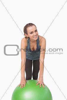 Fit woman supporting herself with a fitness ball