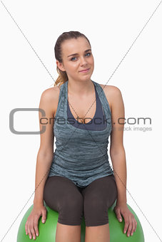 Attractive fit woman sitting on fitness ball