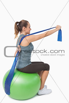 Cute woman stretching her arms with a resistance band