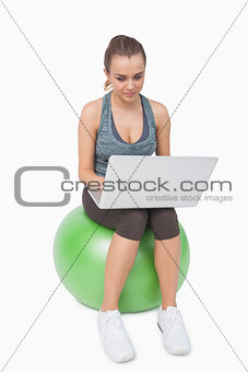 Fit woman using her notebook sitting on balance ball