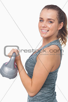 Happy woman training with a kettle bell