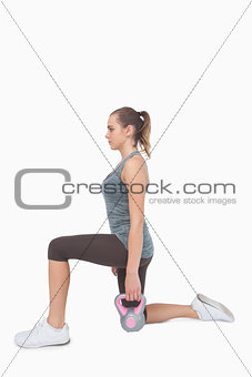 Blonde woman training with kettle bell while lunging