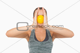 Young woman holding massage ball between hands in front of her face