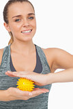 Attractive woman holding yellow massage ball between her hands
