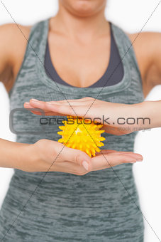 Close up of young woman holding yellow massage ball between her hands