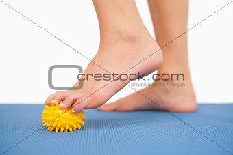Close up of female feet touching yellow massage ball