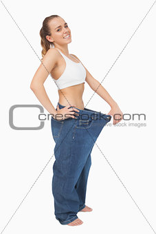 Cute woman wearing too big blue jeans