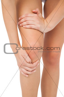 Close up of slim woman touching her injured knee