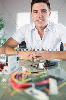 Attractive computer engineer sitting at desk looking at camera