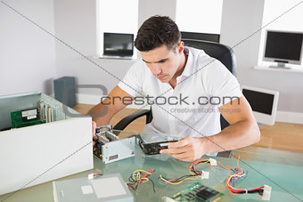 Attractive computer engineer sitting at desk looking at hardware