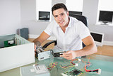 Attractive smiling computer engineer sitting at desk holding hardware