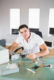 Attractive computer engineer sitting at desk holding hardware