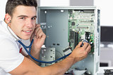 Smiling computer engineer examining hardware with stethoscope