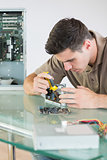 Handsome focused computer engineer repairing hardware with pliers