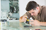 Handsome serious computer engineer repairing hardware with pliers