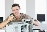 Handsome cheerful computer engineer repairing open computer