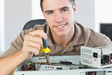 Handsome content computer engineer repairing open computer