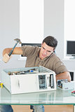 Handsome angry computer engineer destroying computer with hammer