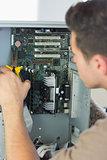 Computer engineer repairing open computer with pliers