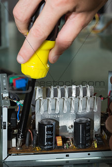 Close up of hands repairing hardware with screw driver