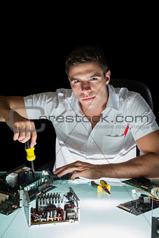 Attractive computer engineer working by night with screw driver
