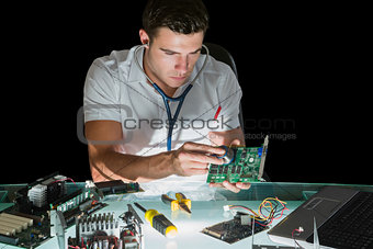 Attractive computer engineer examining hardware with stethoscope