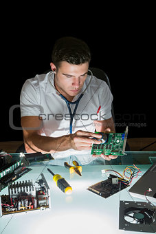 Attractive computer engineer examining hardware with stethoscope by night