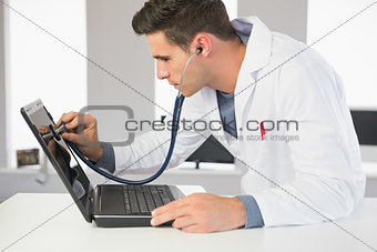 Attractive focused computer engineer examining laptop with stethoscope