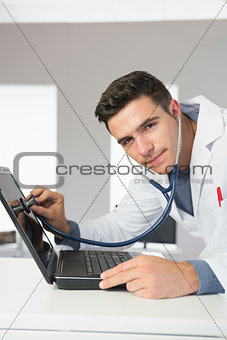Attractive content computer engineer examining laptop with stethoscope