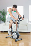 Sporty handsome man training on exercise bike